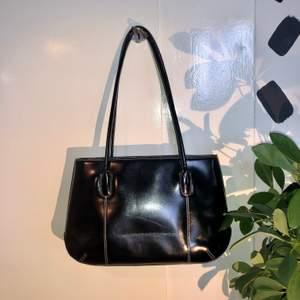 Ascool svart väska med vita sömmar. Använt skick. Skavda handtag (se bild 3). Mått: ca 22x34cm+handtagen. ❗️Köparen står för frakten❗️Fråga om du har några funderingar🌸🌟