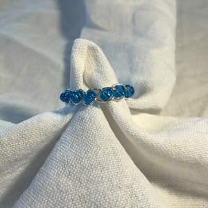 En hemmagjord ring med massor små blåa pärlor och metalltråden i färgen silver. Fin att ha till blåa, vita och beicha kläder.