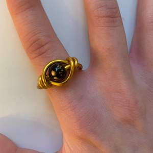 Ring av guldig ståltråd och en svart/guldspräcklig pärla⚫️✨