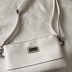 En vit Duffy väska med fickor både utanpå och inuti ( nypris 200kr ) det finns både ett kort band för handväska och ett långt band till axelväska💓 använd en gång