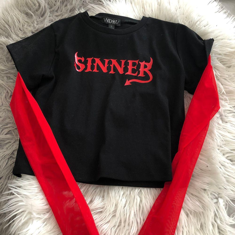 Croppad tröja från Dollskill med röda mesh ärmar och röd text. Är en L men sitter ganska tight, kanske mer som S/M. Köptes för ca 299 och är använd endast en gång.. Toppar.