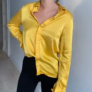 gul oversized satinskjorta från na-kd i storlek 36, fint skick, köparen står för frakten