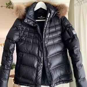 """Säljer en svart vinterjacka från märket """"Mountain Works"""" i äkta päls och dun. Pälsen är avtagbar. Har dragkedjor på  fickorna samt så man kan spänna åt jackan längst ner så som man vill ha den. Storlek S, passar även XS. Säljer för 800 kr. Köparen står för frakten!"""