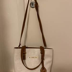 En väska antagligen Fake mikeal kors. I bra skick, fåtal gånger använd, säljer pga att den inte används. Vit och brun med guld detaljer. Priset kan diskuteras😊