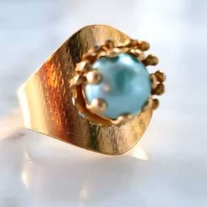 Guldfärgad ring med blå pärla. Supercool att ha med ett par mindre guldfärgaderingar.😇Kontakta vid intresse.