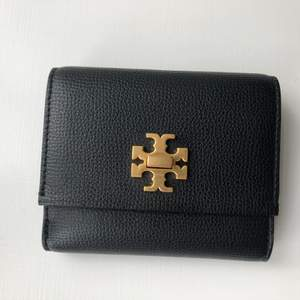 Svart plånbok med gulddetaljer från Tory Burch med mycket plats för kort och lösa pengar. Äkta. Nypris ca 1300kr