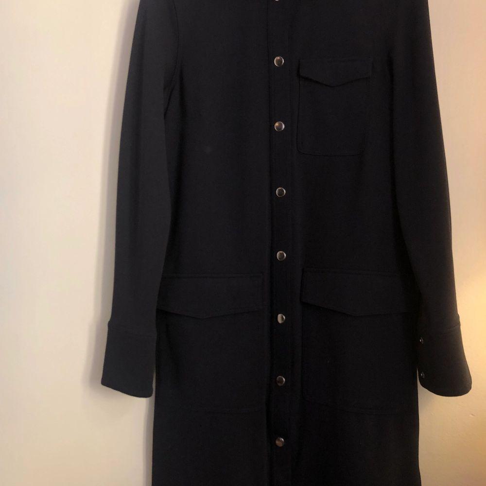 Super fin klänning med knappar och tillhörande band som fästs i midjan. Relativt tjockt tyg. Klänningar.