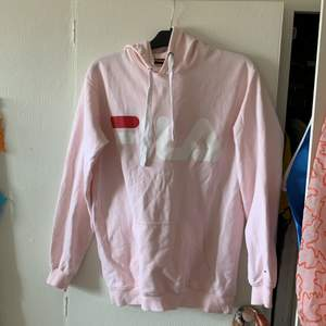 rosa fila-hoodie i storlek S, men generös i storleken. I väldigt bra skick och använd få gånger. Har en lite. Fläck mellan L och A, se bild 2. Går säkert att ta väck! Jättefin rosa färg som är ganska sällsynt❤️🌞