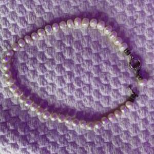 Halsband med vita pärlor och silvrigt knäppe, inga skador eller något