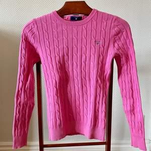 Ljusrosa, figursydd, kabelstickad tröja från Gant i storlek xxs, 32. Tröjan är köpt av mig i en Gantaffär och är i nyskick, använd 2 gånger.  Material: bomull, polyamid, elastan