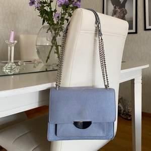 Blå väska som är liten men endå får plats med rimligt mycket i sig. Bra skick.