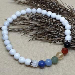 Ett pärlarmband med en pärla för varje chakra. Chakrastenarna är bergskristall, sodalit, angelit, aventurin, citrin, karneol, obsidian. Runtom är det howlitpärlor ❤️