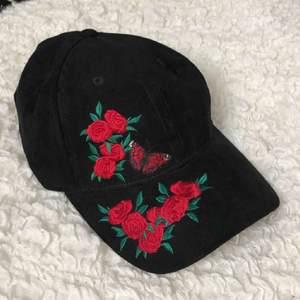 svart keps i mocka imitation med broderade rosor