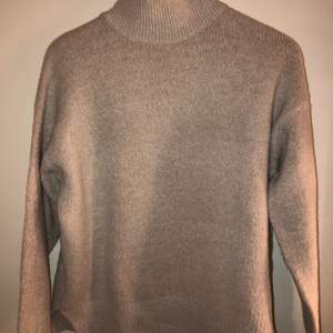 En gosig ljust beige stickad tröja med krage. Inte alls stickig utan är i ett mjukt och varmt material. Otroligt skön och fin med liten kort slits på sidorna!