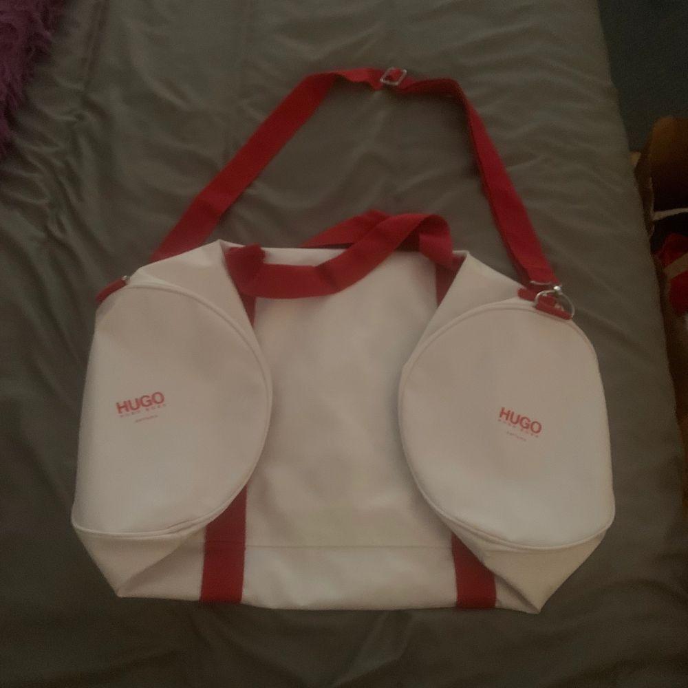 Säljer en stor väska, vit, nästan som skinn, röd där inne, liten ficka inuti. Kan användas som träningsväska. Hugo boss parfums. Bra skicka. (Dåliga bilder pga min kamera) . Accessoarer.