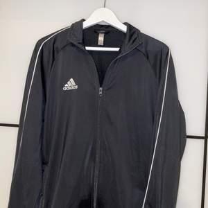 En svart kofta från adidas med vita stripes på sidan av ärmarna. Tröja är i storlek L.