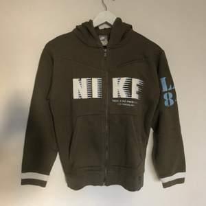 Vintage Nike Zipup Hoodie från tidiga 2000-talet. Tröjan är i mörkgrönfärg. Har en ficka ovanför vänstra bröstet. Påminner mig om y2K stilen. Passar som en Small