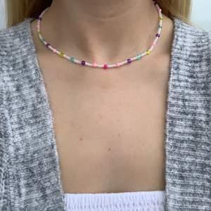 Vitt pärlhalsband med flerfärgade pärlor🤍💜💞🦋🥳 halsbandet försluts med lås och tråden är elastisk