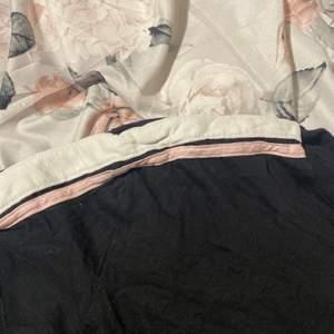 En svart t-shirt med vit rosa ränder vid armarna.