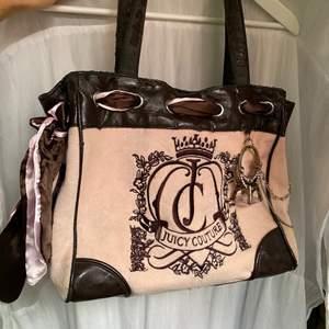 juicy couture väska i beigerosa med brunt läder. inte bästa skicket, missfärgningar på tyget samt slitningar på lädret (se skick utifrån bilderna). väskan är juicys gamla 2000s modell som inte säljs längre💋köptes på plick men har själv aldrig använt