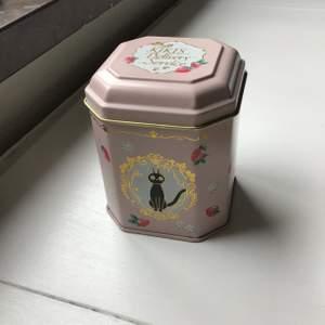Sockersöt burk med motiv från Kikis Expressbud. Har en liten slitning på locket (se bild). Cirka 10 cm hög, 6 cm bred.