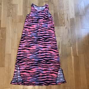Säljer denna fina klänningen ifrån Lindex kids. Använt en gång. Fint tiger mönster med coola färger!! Klänningen har två slitsar på vardera sida om klänningen, mycket fin detalj. Klänningen har även en ficka som jag visade på en av bilderna! Storlek 146/152. Kontakta mig vid fler bilder och frågor❤️