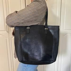 Svart väska från Don Donna. Ett innerfack med dragkedja och två ytterligare innerfack utan dragkedja. Går att stänga hela väskan med en dragkedja. Lite små sliten i vissa hörn, men utöver det är den i bra skick. Höjd: 33cm, bredd: 40 cm, djup: 14 cm.