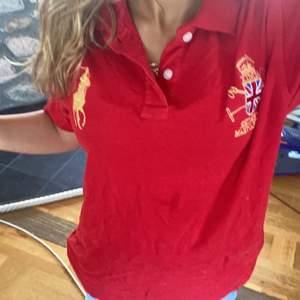 En röd Polo tröja,Med en trea bak på tröjan(:
