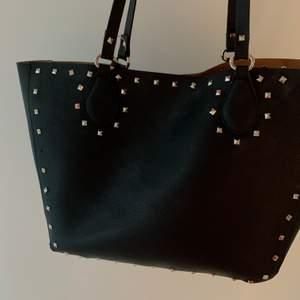 Säljer denna fina svarta väskan med nitar på, lik väskan ifrån valentino. En nit har ramlat av men inget man tänker på, rymlig och super cool! Mitt pris är 300 kr.