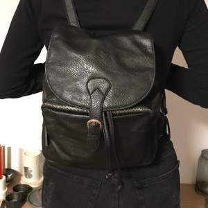 """Black vegan leather drawstring closure backpack. Can fit an iPad Pro (10"""")  or Air. Great used condition. Magnetic clasp. No fading, loose stitching, holes, tears, rips, snags. Lining is great. Please note the inside of the flap. Smoke and pet free storage space. No other flaws to note.  Happy to bundle. Will gladly take more pics. Disclaimer: Please expect some general wear in all secondhand pre-loved items as they have lived a previous life, so don't expect a mint item."""