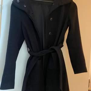 En fin svart kappa från Filippa k som knappt är använd, fin till hösten . Den håller värmen bra och är både fin öppen och stängd .