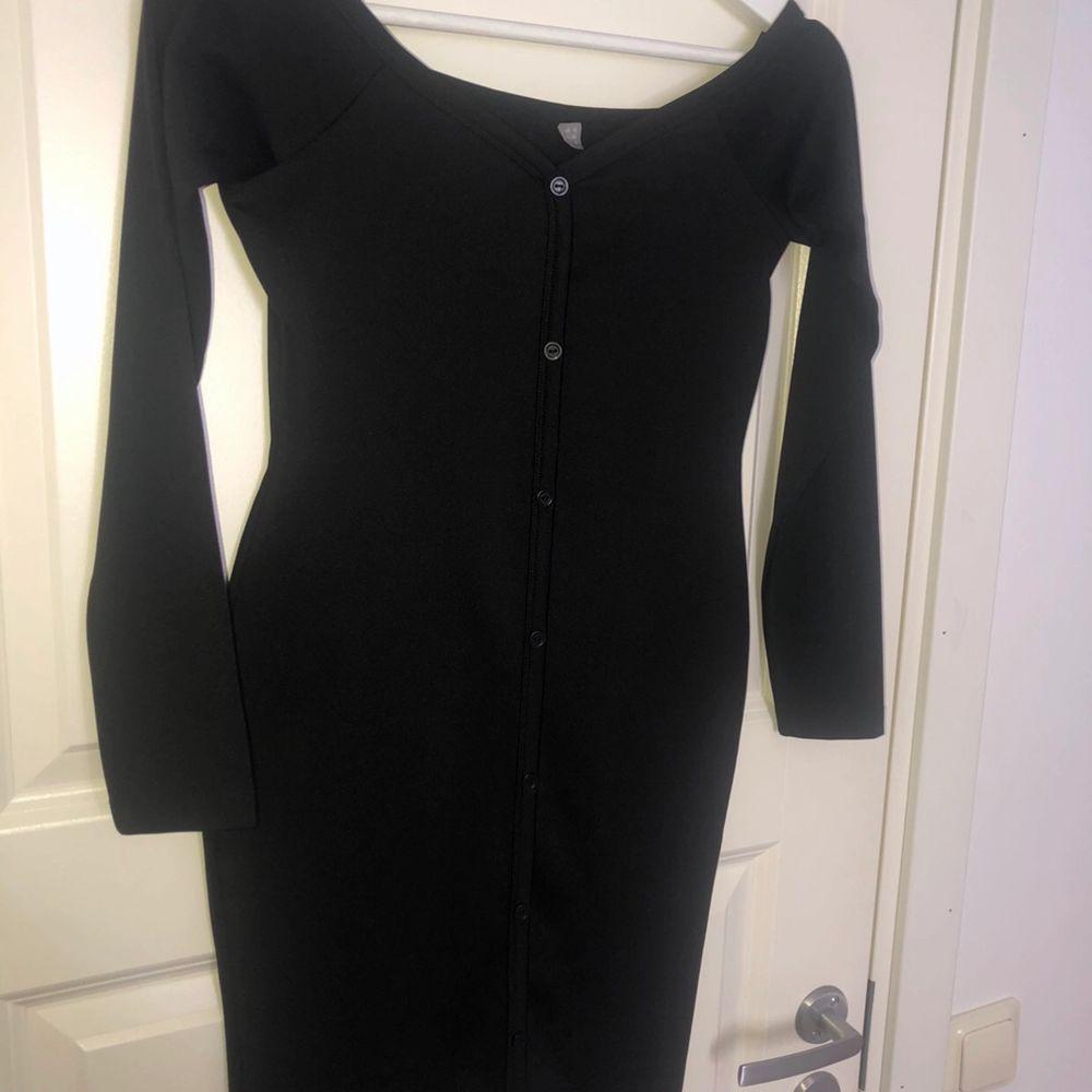 Nyskick klänning svart med knappar längs framsidan. Klänningar.