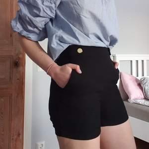 Stiliga svarta tygshorts med guldiga detaljer. Dragkedja på sidan. Tips! Köp hela outfiten och bli riktigt sommarfin. Toppen är också till salu(; Frakt tillkommer
