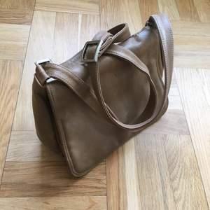 Snygg grönbeige axelremsväska i äkta skinn. Tjockt, följsamt läder i hög kvalitet. Vintage, men i fint skick! Storleken är 25 x 20cm