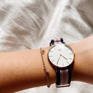En fin DW klocka med ett roséguld ur och ett marinblått, rosa och vitt band till. Ursprungligt pris ca 2 000 kr. Fint skick och säljs med samma förpackning som nyköpt. Icke fungerande i nuläget men otroligt fin som smycke till sommaren.