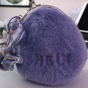 """En lila plånbok med scrunchie från """"SHEIN"""". Den är 90% polyester och 10% iron. Längd 12 cm, bredd 7 cm, höjd 14 cm. Fick den i februari 2021 och har aldrig lagt något i den 🌱✨"""