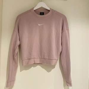 Blekrosa sweatshirt med öppen rygg, croppad.