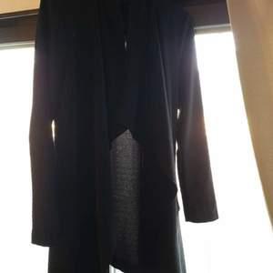 En jacka som är i ett tunnare material. Den passar perfekt till sommarkvällar när solen börja gå ner. Jackan är ner till knänen och har en fin form, som formar sig till kroppen.