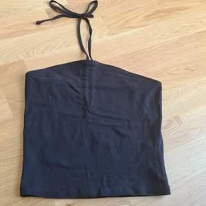 Ett svart kort linne med snörknytning runt hals. Oanvänd så i nyskick. Köparen står för frakten.