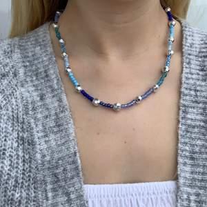 Blått pärlhalsband med silvriga discokulor🦋💙🤍 halsbandet försluts med lås och tråden är elastisk