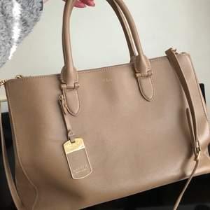 Supersnygg, stor och äkta Ralph Lauren väska i äldre modell. Har en axelrem och kan därmed bäras både som handväska och axelremsväska. Väskan är ganska flitigt använd men i mycket fint skick! Den är stor och rymlig och en MacBook får plats utan problem. I äkta skinn. 🌸