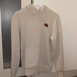 Snygg beige hoodie med en ros från H&M killavdelningen🖤 stl XS men sitter som en S/M beroende på hur man vill att den ska sitta! Använt några gånger, inga fläckar eller så. Säljs pga har för många hoodies:( frakt tillkommer!!