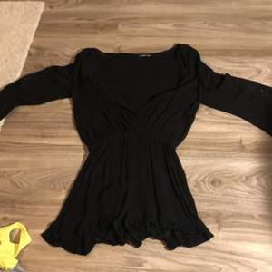 Svart jumpsuit i storlek XS. Säljer pga att den inte används, använd ett fåtal gånger utomlands. Perfekt till sommaren. Mönster vid armarna och knappar vid bröstet så den går att knäppa.