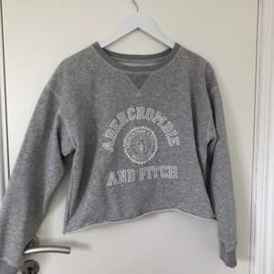 Grå, aningen croppad sweatshirt från Abercrombie & Fitch. Använd fåtal gånger, därav nyskick! 🌟 Köptes för ca 500kr. Passar en med storlek XS-M.