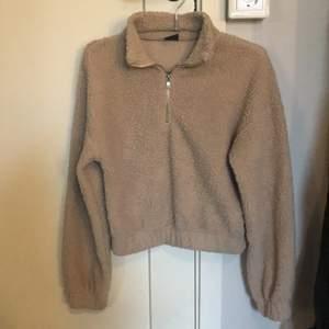 En beige croppad tröja med dragkedja med teddy material. Den ganska tunn. Storlek XS. Dm om ni är intresserade.