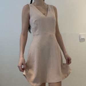 Klänning med detaljer baktil                                          Pris + frakt vid leverans