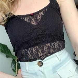 Ett svart spets-linne med en gullig rosa rosett! Superfint skick och så snygg alla årstider! Passar XS-S.