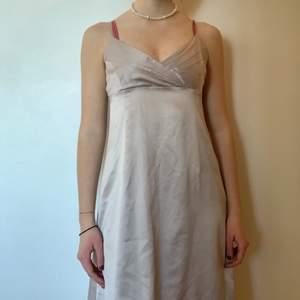 En vacker klänning!! Glansigt material med beige färg. Perfekta längden och väldigt snygg passform. Köpt på secondhand men har aldrig använt den, så den är i gott skick!