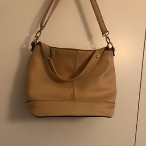 Läderimitation beige väska. Bra skick. Axelremmen kan kortas in till hälften.