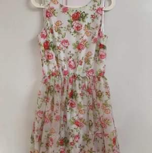 Vacker blommig klänning med urringning bak på klänningen. Använd endast en gång. Kan mötas upp eller frakta